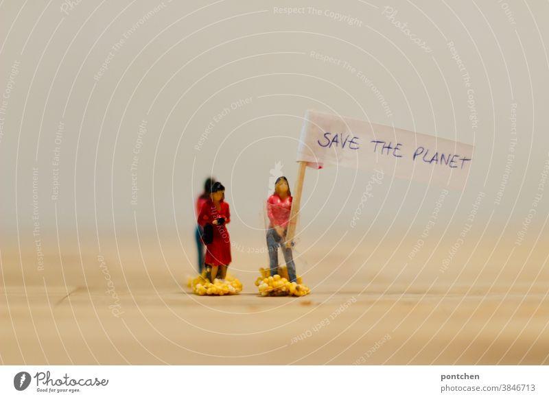 """Demonstration. Frau hält ein Transparent hoch auf dem """"Save the Planet"""" steht. Klimawandel, Klimaschutz frauen figuren transparent schild klimaschutz"""