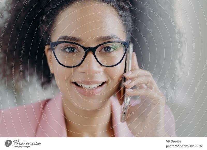 Nahaufnahme eines Porträts einer glücklichen dunkelhäutigen Geschäftsfrau, die ihr Handy ans Ohr hält, einen Geschäftspartner anruft, ein charmantes Lächeln hat, eine optische Brille trägt, lockiges buschiges Haar hat und über Arbeitsfragen spricht