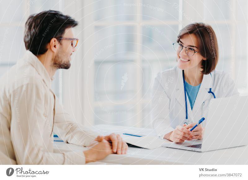 Geschulte Allgemeinärztin erklärt Diagnose und berät Patientin, zeigt Informationen am Laptop, posiert im klinischen Büro, bespricht Scan-Ergebnisse im Diagnosezentrum