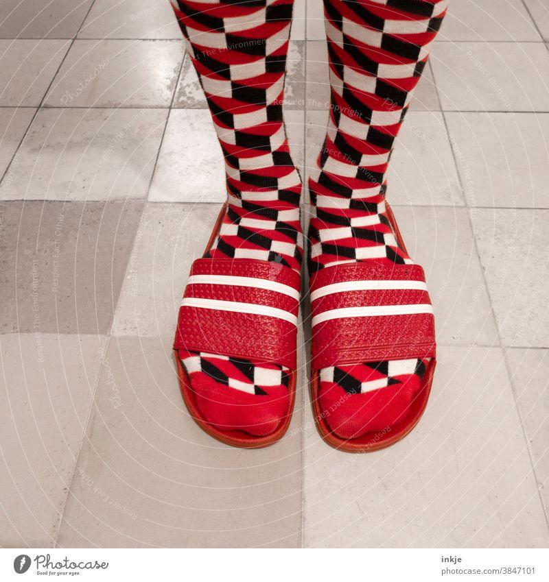 Gemusterte Socken in roten Badelatschen Farbfoto Nahaufnahme Vogelperspektive Fuß Füße Mode Stil geschmacklos aussergewöhnlcih anders hässlich gewagt weiß
