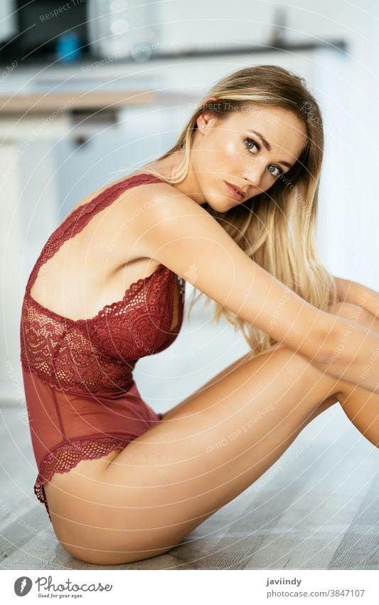 Junge erwachsene kaukasische Frau in roten Dessous auf dem Boden sitzend Erwachsener attraktiv schön Schönheit Schlafzimmer schwarz blond Körper Boudoir