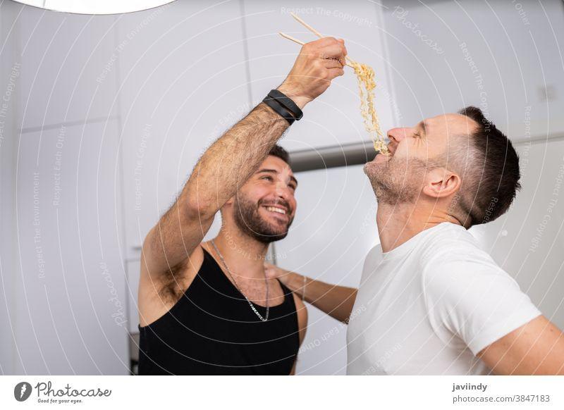 Mann gibt seinem Freund auf lustige Weise Nudeln zu essen schwul Paar Männer Homosexualität Spaghetti Spätzle Lebensmittel Essen zubereiten Küche lgbt Liebe