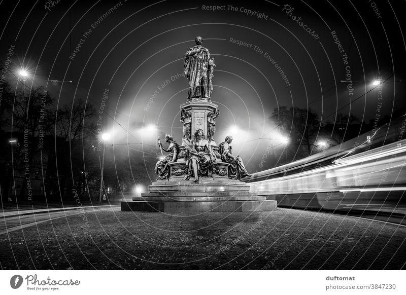 Schwarzweiß Foto mit Langzeitbelichtung eines Denkmals bei Nacht Schwarzweißfoto Straßenbahn Licht München Berufsverkehr Statue verschwommener hintergrund Abend