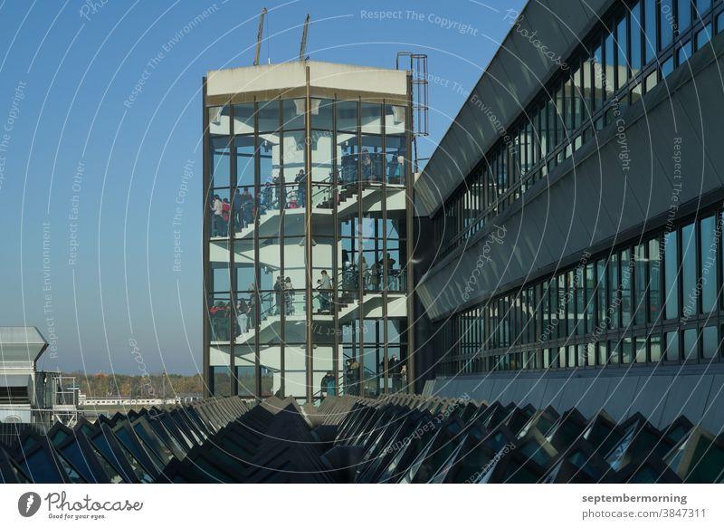 Turm aus Glas, innenliegende Treppen, viele Menschen auf den Stufen, hellblauer Himmel, Gebäudekomplex schließt an den Turm, Stahlkonstruktion Turm durchsichtig