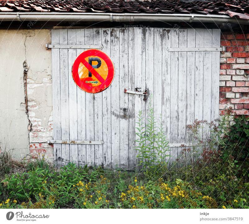 Parkverbotsschild am Holztor im Hinterhof farbfoto Außenaufnahme Menschenleer Schild Verbotsschild Garage verwildert rot Unkraut Schilder & Markierungen Mauer