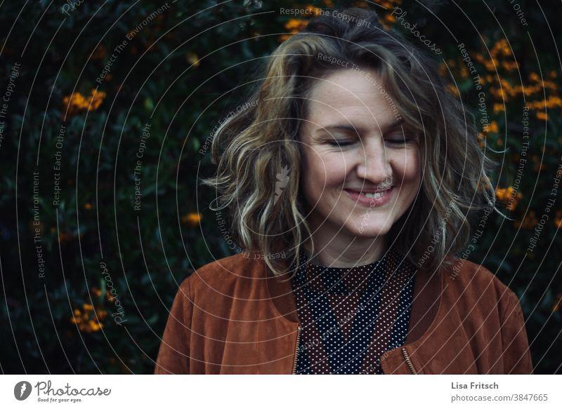 FRAU - GRINSEN - AUGEN ZU Frau Locken blond jung Augen geschlossen frech grinsen Erwachsene 30 Jahre alt Porträt Freude Fröhlichkeit feminin Außenaufnahme