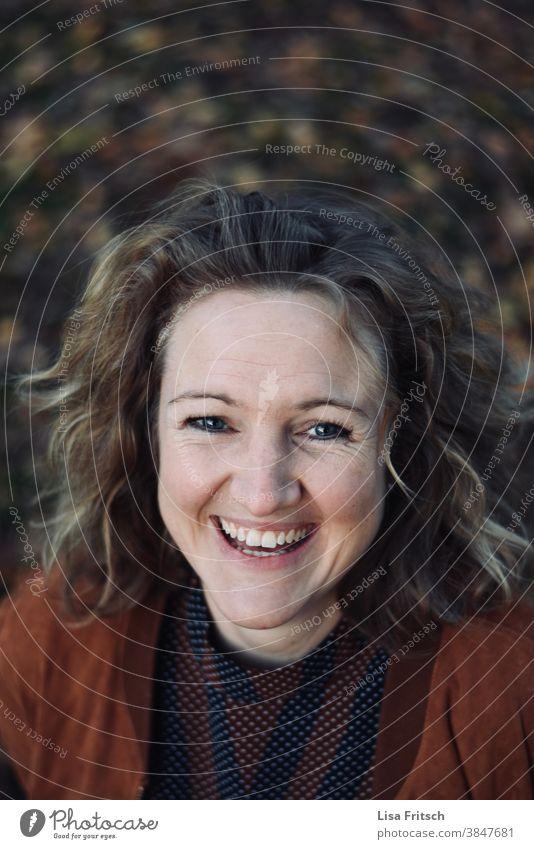 FRAU LACHEND ZWISCHEN LAUBBLÄTTERN Frau Locken blond Haare & Frisuren Herbst laub braun herbstlich Herbstfarben lachen Fröhlichkeit Erwachsene Außenaufnahme