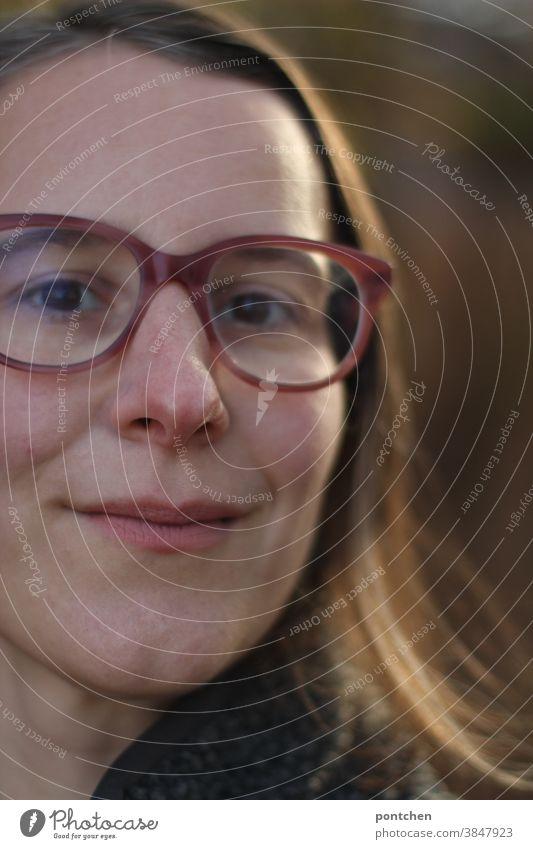 Gesicht einer leicht lächelnden Frau mit brille und braunen haaren. Zufriedenheit natürlich Blick in die Kamera grübchen brünett Brille Nahaufnahme Erwachsene