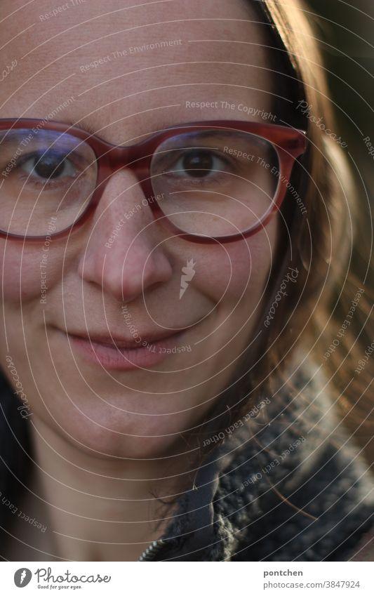 Gesicht einer lächelnden, brünetten Frau mit Brille. Zufriedenheit glücklich freundlich zufrieden Erwachsene Nahaufnahme haare grübchen Blick in die Kamera
