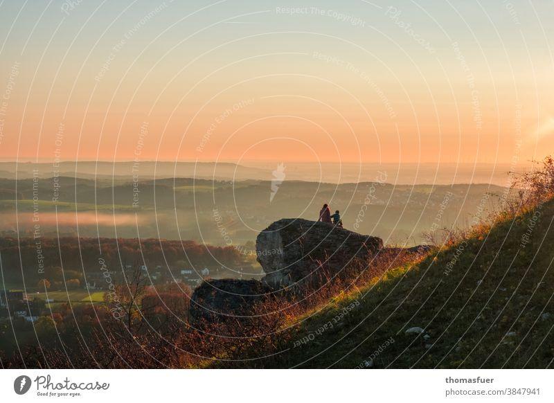 Paar auf einem Felsen sitzend schaut in die Weite und betrachtet den Sonnenuntergang Schönes Wetter Sonntag Herbst Himmel Farben Berg Mutter Kind schauen Natur