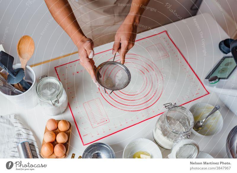 Hände eines Mannes, der Mehl durch ein Sieb auf dem Tisch sichtet. Eier Bäckerei Desserts Butter Salz Lebensmittel Essen zubereiten heimwärts hausgemacht