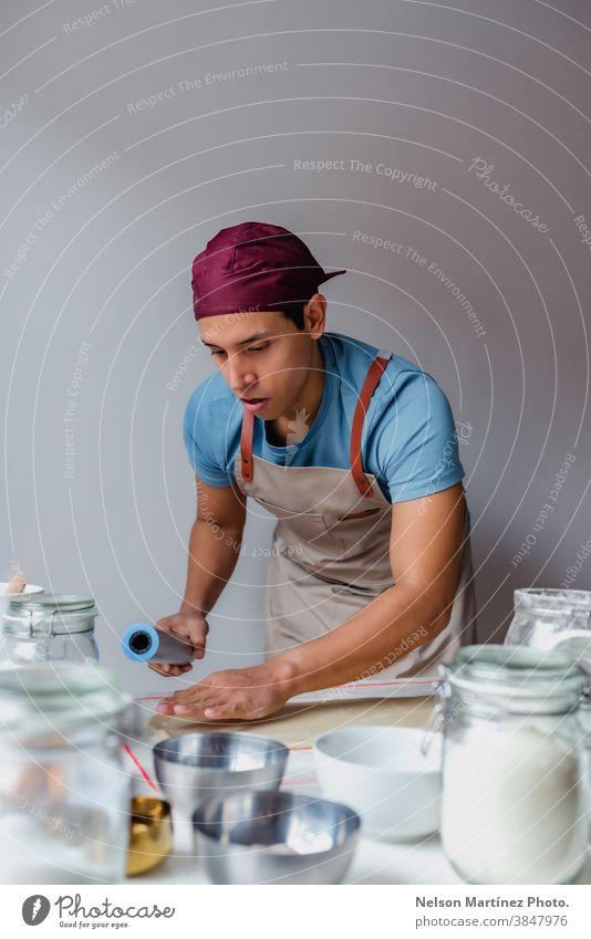Mann, der Teig über einen weißen Tisch knetet. Erwachsener im Innenbereich Essen zubereiten Teigwaren Mehl Küchenchef Restaurant Beschäftigung Lebensmittel Eier