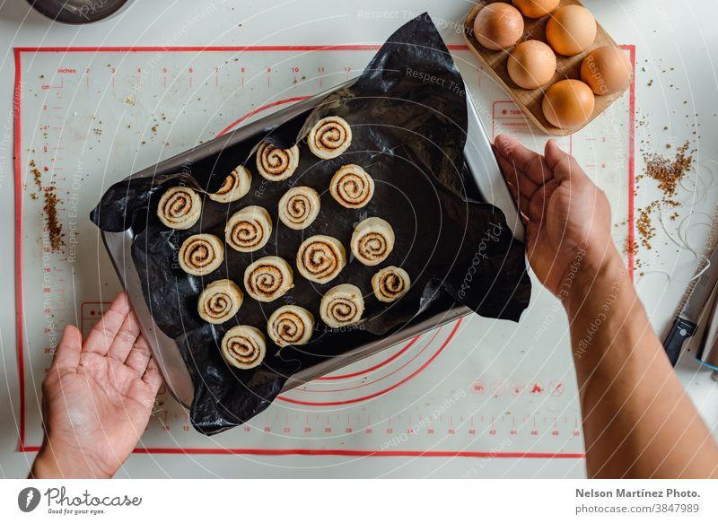 Die Hand eines Mannes hält ein Tablett mit Zimtbrötchen, die bereit sind, in den Ofen geschoben zu werden. im Innenbereich Essen zubereiten Teigwaren Mehl