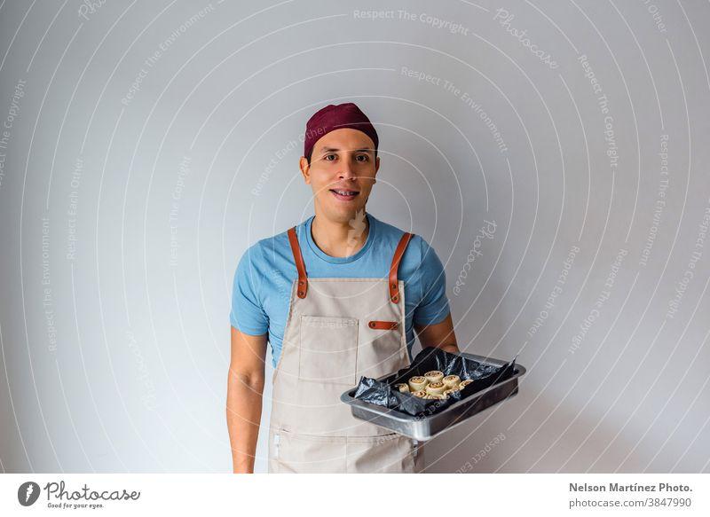 Ein spanischer Mann hält ein Tablett mit Zimtrollen auf weißem Hintergrund. Erwachsener im Innenbereich Essen zubereiten Teigwaren Mehl Küchenchef Restaurant