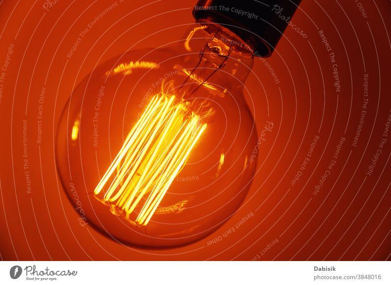 Vintage-Glühbirne auf orangem Hintergrund, Nahaufnahme. Glühende Edison-Glühbirne Knolle Licht altehrwürdig Lampe Design weiß kreativ Konzept Idee Farbe