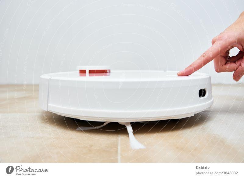 Handdruck-Starttaste am Roboter-Staubsauger. Moderner intelligenter Haushalt Vakuum Raumpfleger Kontrolle klug dreckig heimwärts automatisch Geräte täglich