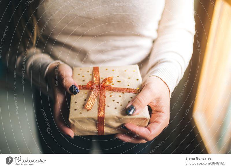 Junge Frauen mit Glitzernägeln, die eine Weihnachtsgeschenkschachtel halten und sie in der Kamera zeigen. Hände halten eine Neujahrsgeschenkschachtel, die mit Bastelpapier, rotem und goldenem Band und Sternen dekoriert ist. Konzept für Familiengeschenke.