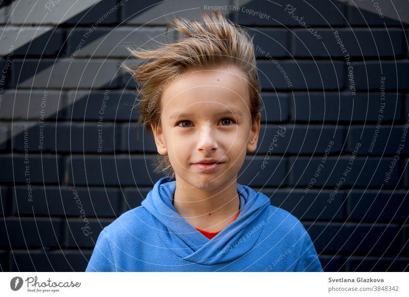 Lustiges Porträt eines blonden, kaukasischen Jungen, dessen Haar sich hebt und im Wind fliegt. Schaut in die Kamera lustig Kind Kindheit Hintergrund Glück