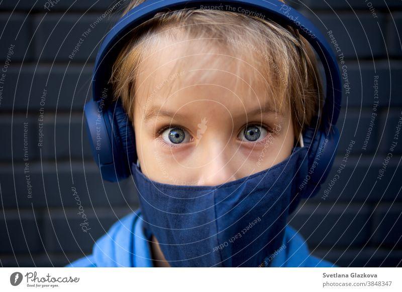 Nahaufnahme des Gesichts eines blonden kaukasischen Jungen. Schaut in die Kamera. Bekleidet mit einer medizinischen Schutzmaske und blauen Kopfhörern Auge