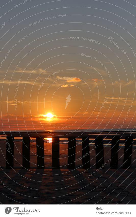 Sonnenuntergang am Strand hinter der Buhne Sonnenlicht Abendsonne abends Wangerooge Abenddämmerung Himmel Wolken Natur Gegenlicht Meer Wasser