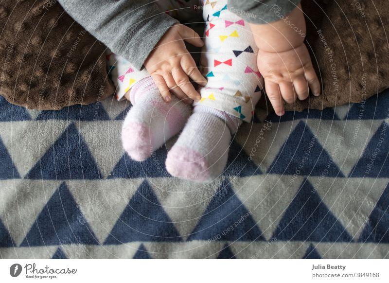 Baby, das nach den Füßen greift, Babyhände mit Grübchen, Decke und Hose mit Dreiecksdruck Fuß Kind Hand neugeboren Liebe klein Zehen Pflege menschlich Hände