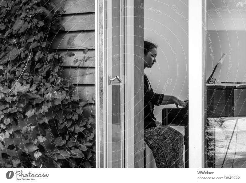 Die Tür zur Veranda steht offen und man kann die junge Pianistin beim Üben belauschen Klavier Flügel Musik Piano Proben Terrasse Balkon draußen Efeu Wand Haus