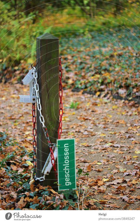 """noch nicht  - Schild """"geschlossen"""" hängt an einer rot-weißen Kette neben einem Holzpfahl, der Weg ist noch zugänglich Verbotsschild Hinweisschild Pfahl"""