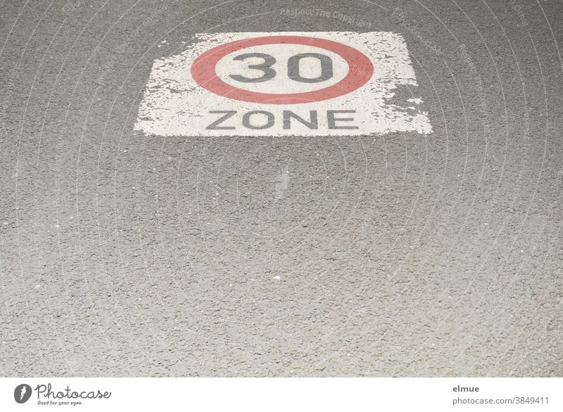 """Auf der asphaltierten Straße ist ein Geschwindigkeitsbegrenzungsschild """"Zone 30"""" aufgemalt / verkehrsberuhigte Zone / langsam fahren / Tempo 30 Verkehrsschild"""