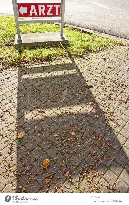 """Rotes Hinweisschild """"ARZT"""" wirft auf dem Fußweg einen Schatten / Orientierung / Wegweiser Arzt Pfeil Straße Schilder & Markierungen Wege & Pfade Zeichen"""