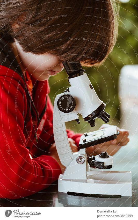 Kind schaut durch ein Mikroskop Aufmerksamkeit Freizeitkleidung Kaukasier Kindheit Konzept Neugier neugierig erkunden Lernen Lifestyle Blick männlich Natur eine