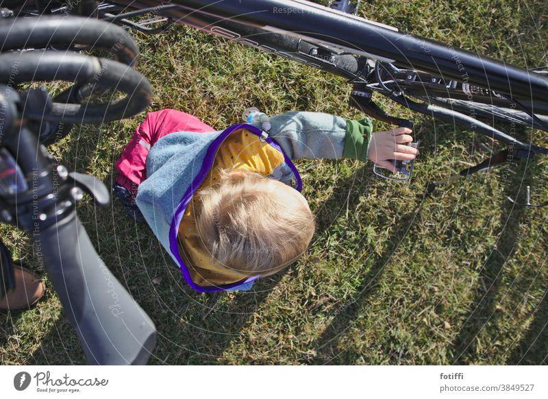 Rad begreifen Kind Fahrrad erfahren drehen Spielen Kleinkind Außenaufnahme Mensch Kindheit Rasen Garten draußen Sommer Glück