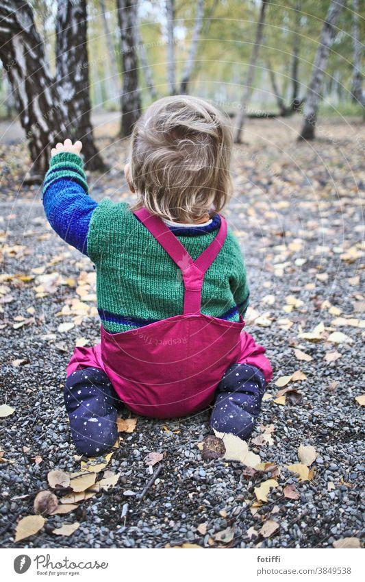 Da geht es lang! Kind Kleinkind Weg Wege & Pfade Wegweiser zeigen hocken Richtung Orientierung links Empfehlung vorschlagen klein niedlich sitzen Regenhose