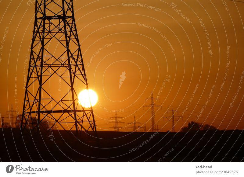 Sonnenuntergang hinter Strommast -oranger Himmel, ein Hochspannnungsmast im Vordergrund, angeschnitten, mehrere Masten im HIntergrund Hochspannungsmast