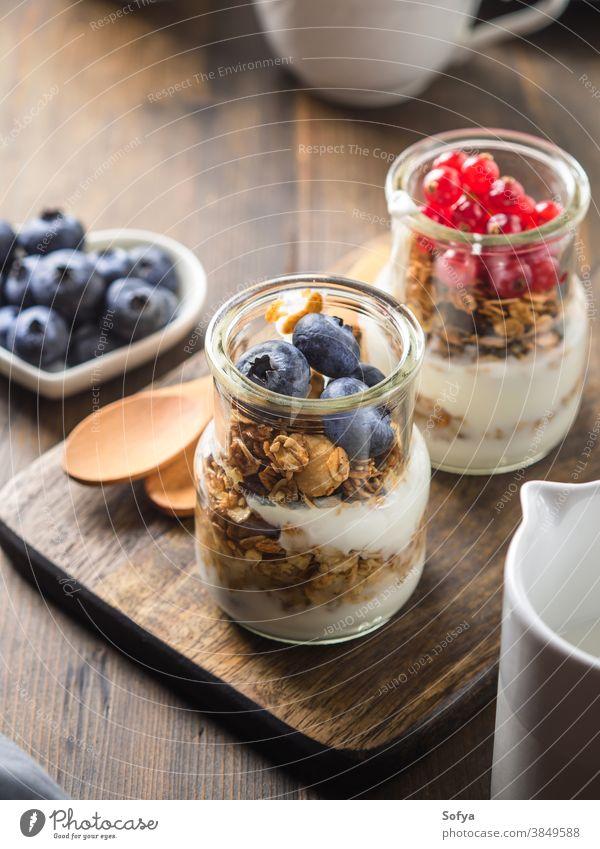 Gemütliches Frühstückskonzept dunkler Holzuntergrund Müsli selbstgemacht Hafer Joghurt Sesam gebacken hölzern Hintergrund Tisch rustikal gemütlich dunkel Kaffee