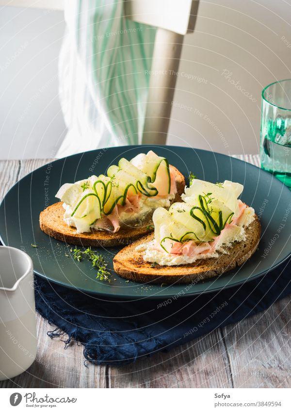 Roggenbrottoasts mit Käse, Schinken, Gurke Belegtes Brot Lebensmittel Salatgurke Gemüse Zuprosten frisch Scheibe Frühstück Kulisse Tisch hölzern schwarz Speise