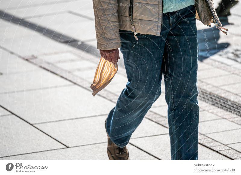 Person, die draußen die Maske in der Hand hält neue Normale Mundschutz mittlere Aufnahme Straße laufen Spaziergang Tag sonnig Frühling nicht erkennbare Personen