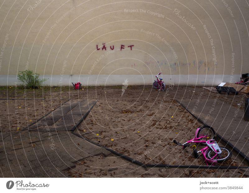 Kunst am Bau, Läuft aus Hinterhof Brandmauer Sandkasten Kinderfahrrad unordentlich herbstlich Morgendämmerung Spray Wort trist Architektur Gedeckte Farben