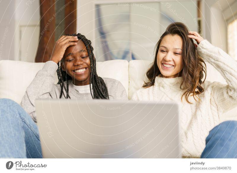 Zwei Studentinnen, die zu Hause mit einem Laptop auf der Couch sitzen. Frauen Freund multiethnisch Computer rassenübergreifend Liege Schüler schwarz Afro-Look