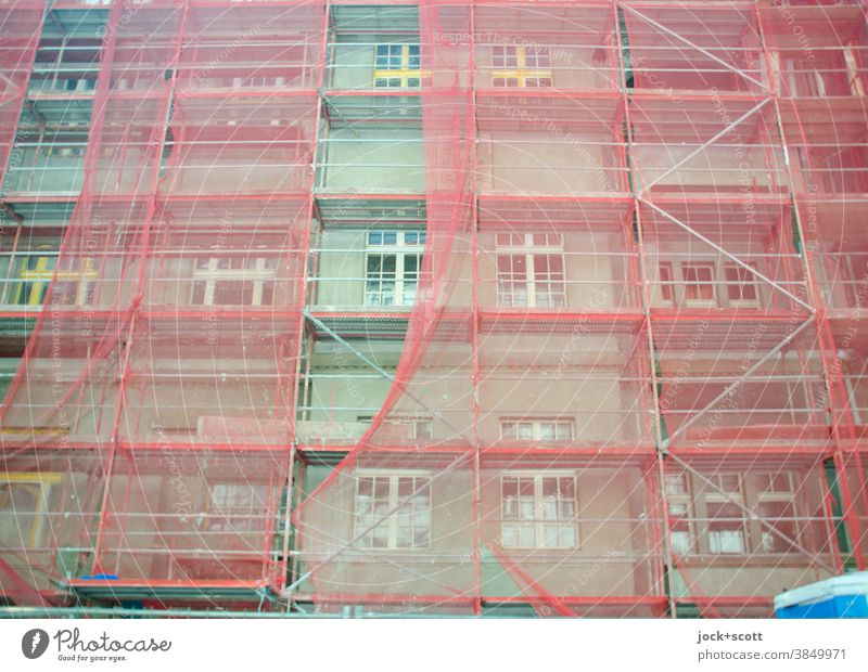 Grüner wohnen, Baustelle mit rötlichen Baugerüst Fassade Abdeckung Schutz authentisch Strukturen & Formen Sicherheit Sanieren Renovieren Haus Fenster