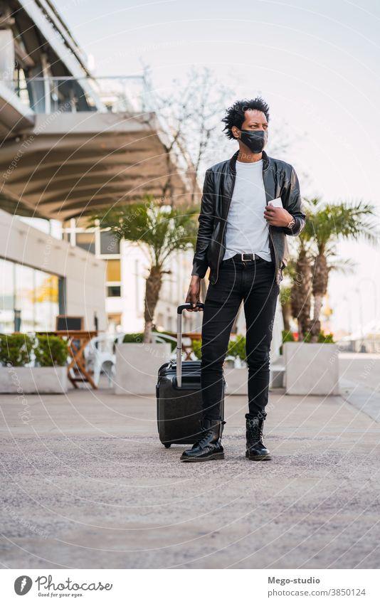 Tourist, der beim Spaziergang im Freien einen Koffer trägt. Afro-Look Mann Reisender Ausflugsziel Konzept Feiertag Tag Freude genießen Abenteuer Ferien Porträt
