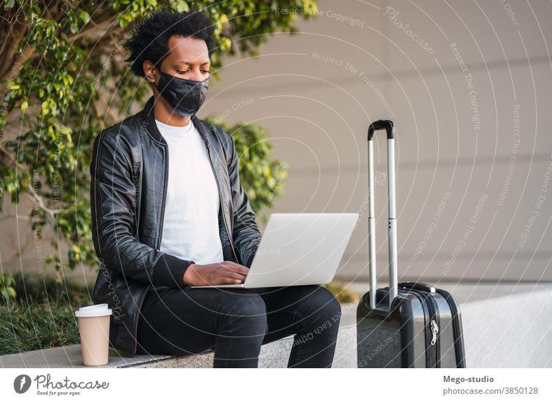 Afrotourist, der seinen Laptop im Freien benutzt. Afro-Look Tourist Mann reisen Schutzmaske Porträt lässig Anschluss Feiertag Tourismus Virus Mundschutz