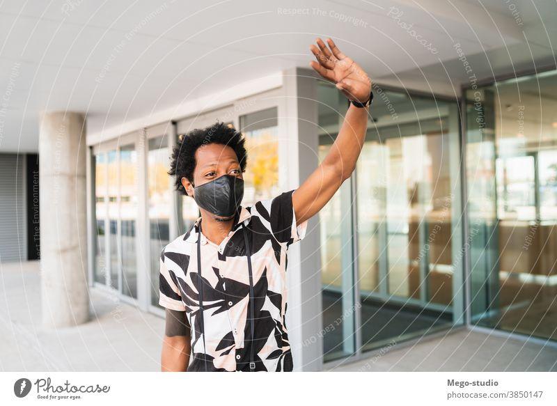 Afrotourist, der auf der Straße ein Taxi ruft. Afro-Look Tourist Mann Reisender Koffer Ausflugsziel Konzept Feiertag Tag Freude genießen Abenteuer Spaziergang