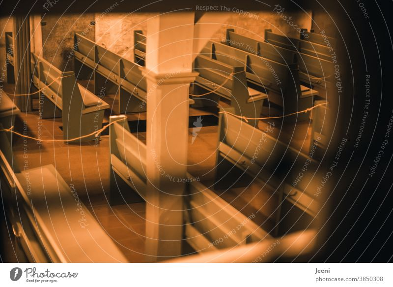 Ein abendlicher Blick durch das Fenster in die leere Kirche - jede zweite Bank ist mit einem Seil abgesperrt - Corona-Pandemie I corona thoughts Kirchenbank