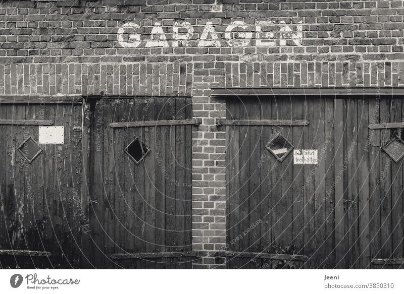 Zwei alte triste GARAGEN Garage Garagentor Garagentore Wand Mauer Backsteinwand Giebel Fassade zwei schwarzweiß Schwarzweißfoto Gebäude menschenleer Haus grau