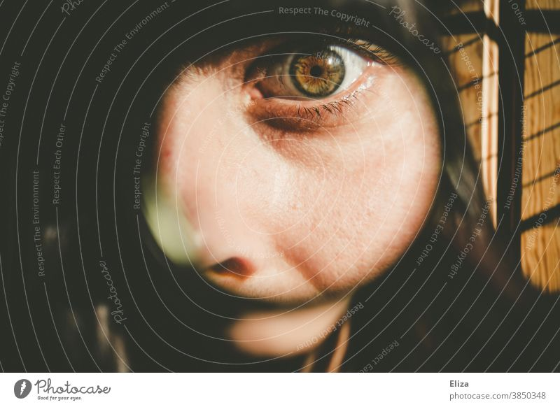 Frau mit großemAuge guckt durch eine Lupe suchen spionieren neuguerig Blick sehen beobachten Mensch vergrößert Blick in die Kamera Detektivin starren Neugier
