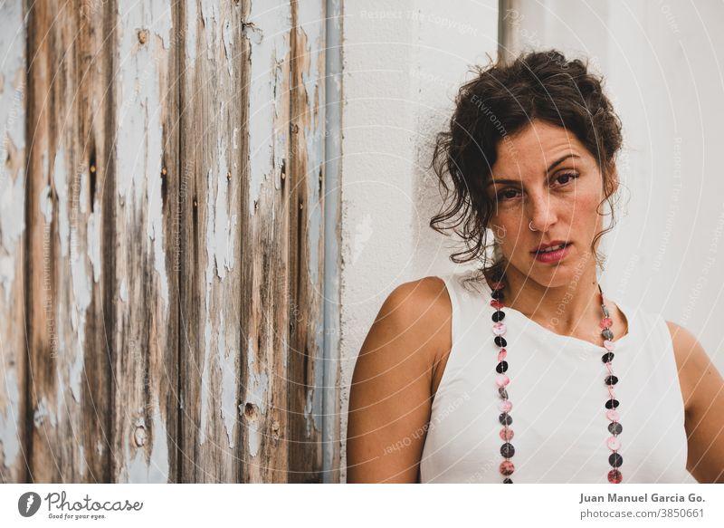 Junge Frau mit Nasenring zeigt zorniges Gesicht hübsch wütend Ring jung Mädchen Charakter ärmellos brünett Ohrringe Reifen abgeplatzt metallisch Halskette