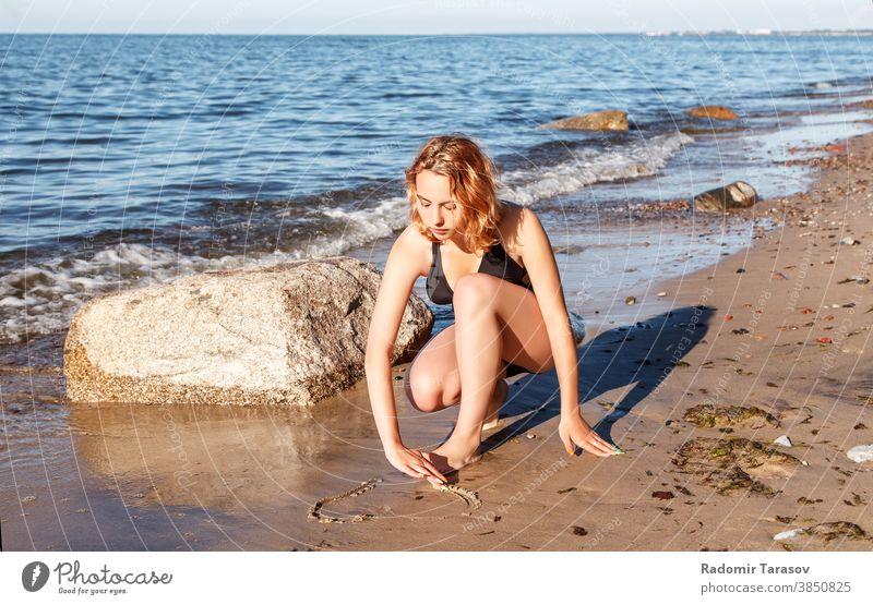 junges Mädchen im Badeanzug zeichnet mit dem Finger auf den Sand am Meeresufer zeichnen Schönheit Glück schön Zeichnung sonnig Frau Wasser Küste Sonne Feiertag