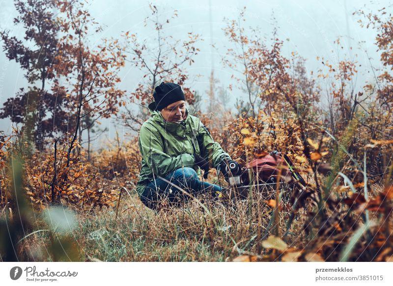 Frau mit Rucksack macht während einer Herbstreise Pause und trinkt am kalten Herbsttag ein heißes Getränk aus der Thermoskanne im Freien Ausflugsziel wandern
