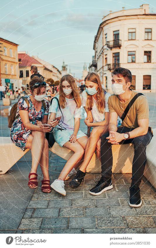 Junge Frauen verbringen Zeit miteinander, indem sie im Stadtzentrum sitzen und die Gesichtsmasken tragen, um eine Virusinfektion zu vermeiden Kaukasier Gespräch