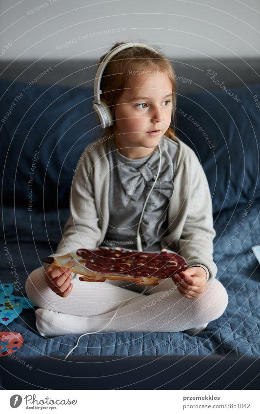 Kleines Mädchen im Vorschulalter lernt online und zeigt ihre zu Hause gezeichneten Arbeiten Kind zuschauend hören Lernen lehrreich Geduldsspiel Bett Internet